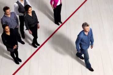 Man crossing a red line showing leadership