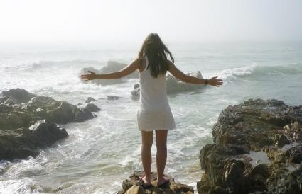 Femme debout sur la côte rocheuse