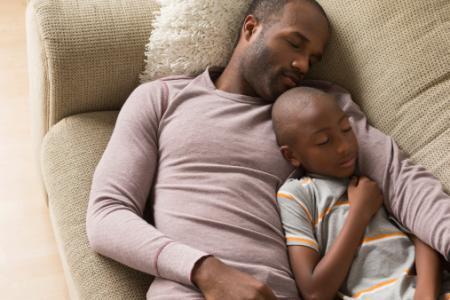Père et fils dormant sur un canapé