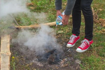 Verser de l'eau sur le feu de camp