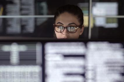 Femme de données entourée de moniteurs