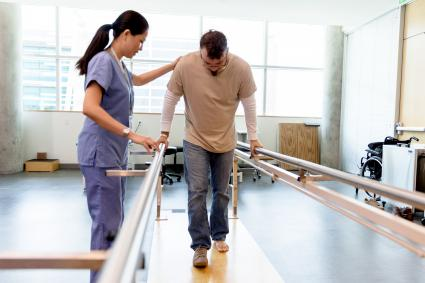 Le patient fait ses premiers pas en utilisant les barres parallèles orthopédiques sous la direction du physiothérapeute
