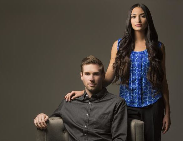 Couple posing by a chair
