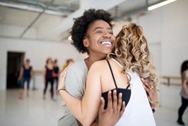 Dance instructor and student hugging