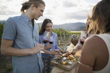 Friends enjoying wine tasting in vineyard