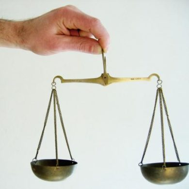 Man balancing set of scales