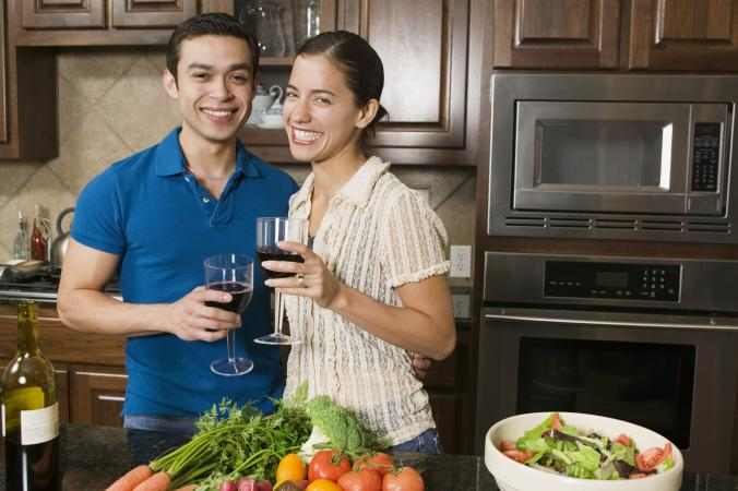 Couple drinking wine while cooking dinner