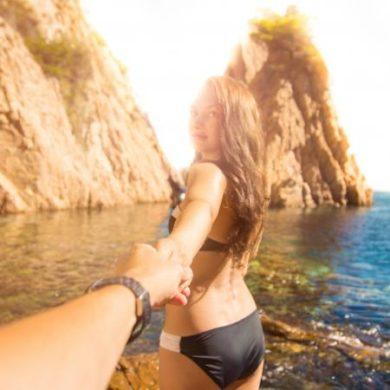 Girl holding boyfriend's hand in Mediterranean Sea