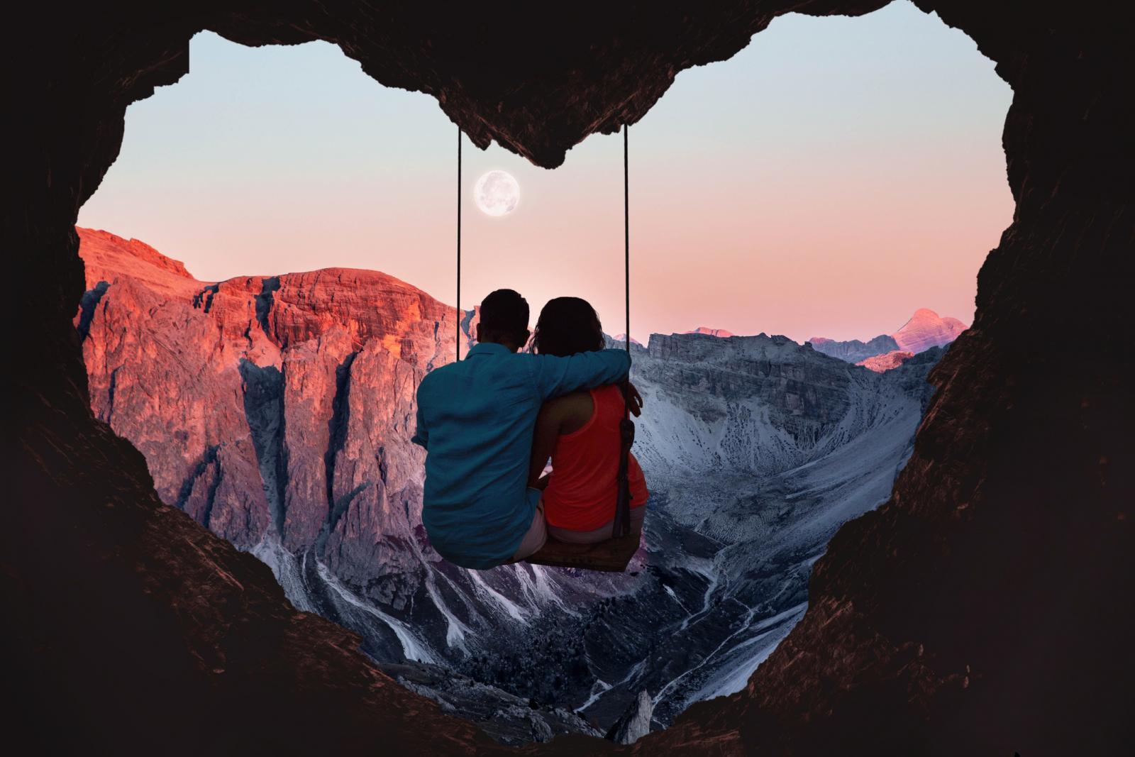 Couple sur la balançoire d'une grotte en forme de coeur et pleine lune