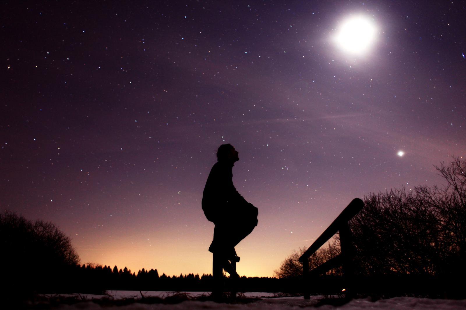 Regarder la lune assis sur le rail d'un petit pont sous un magnifique ciel étoilé