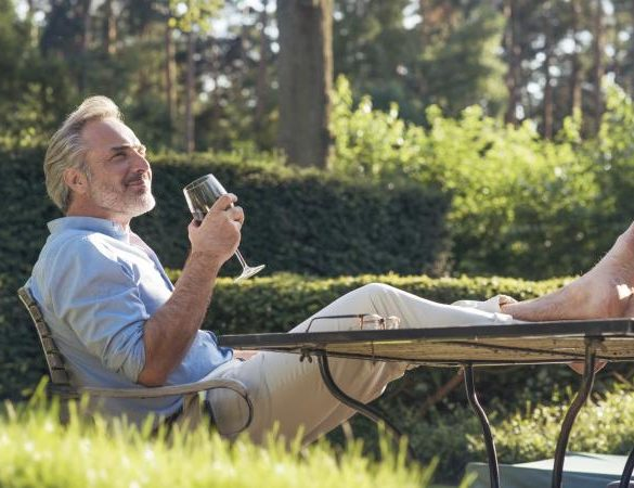 man in garden drinking wine
