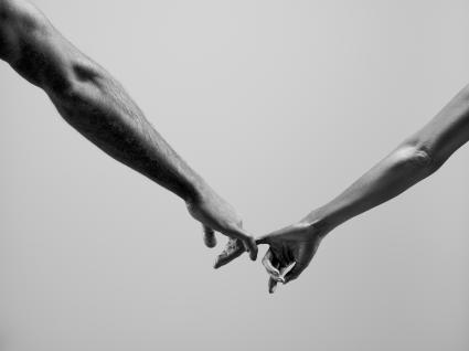 Homme et femme reliant les petits doigts ensemble