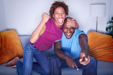 African couple cheering on sofa