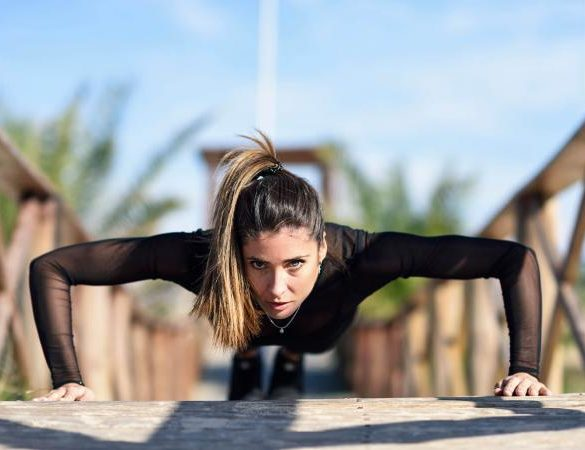 woman doing push-ups on wooden bridge