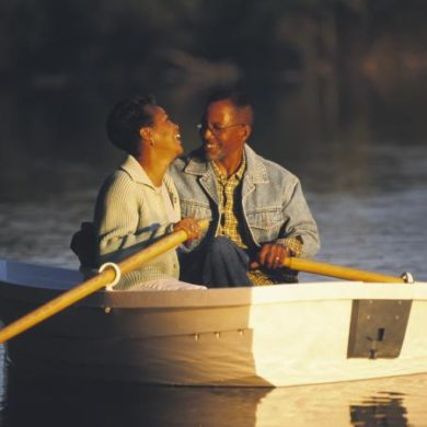 Woman laughing with man in rowboat