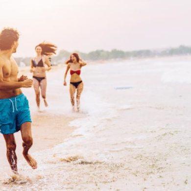 Women chasing a man on the beach