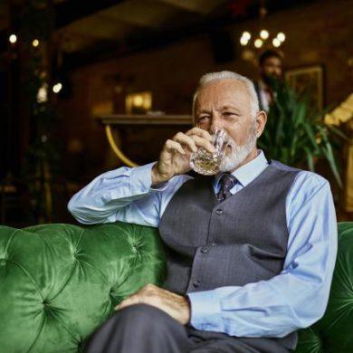 elegant senior man sitting on couch