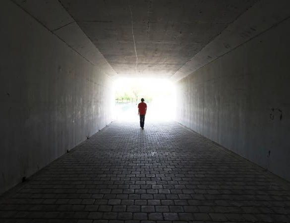 person walking out of a tunnel
