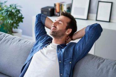 man sitting on sofa daydreaming