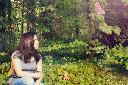 Femme assise sur un sol couvert de lierre en regardant un papillon