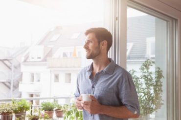 Smiling man looking out of window
